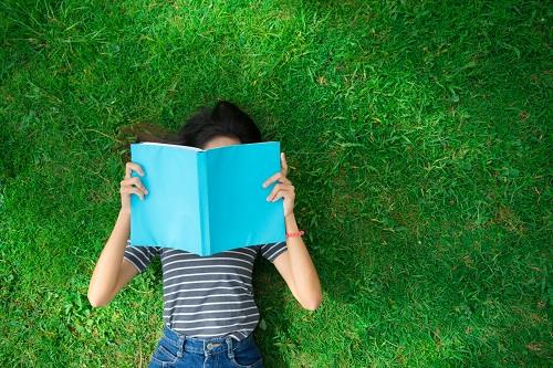 girl laying on grass reading a book